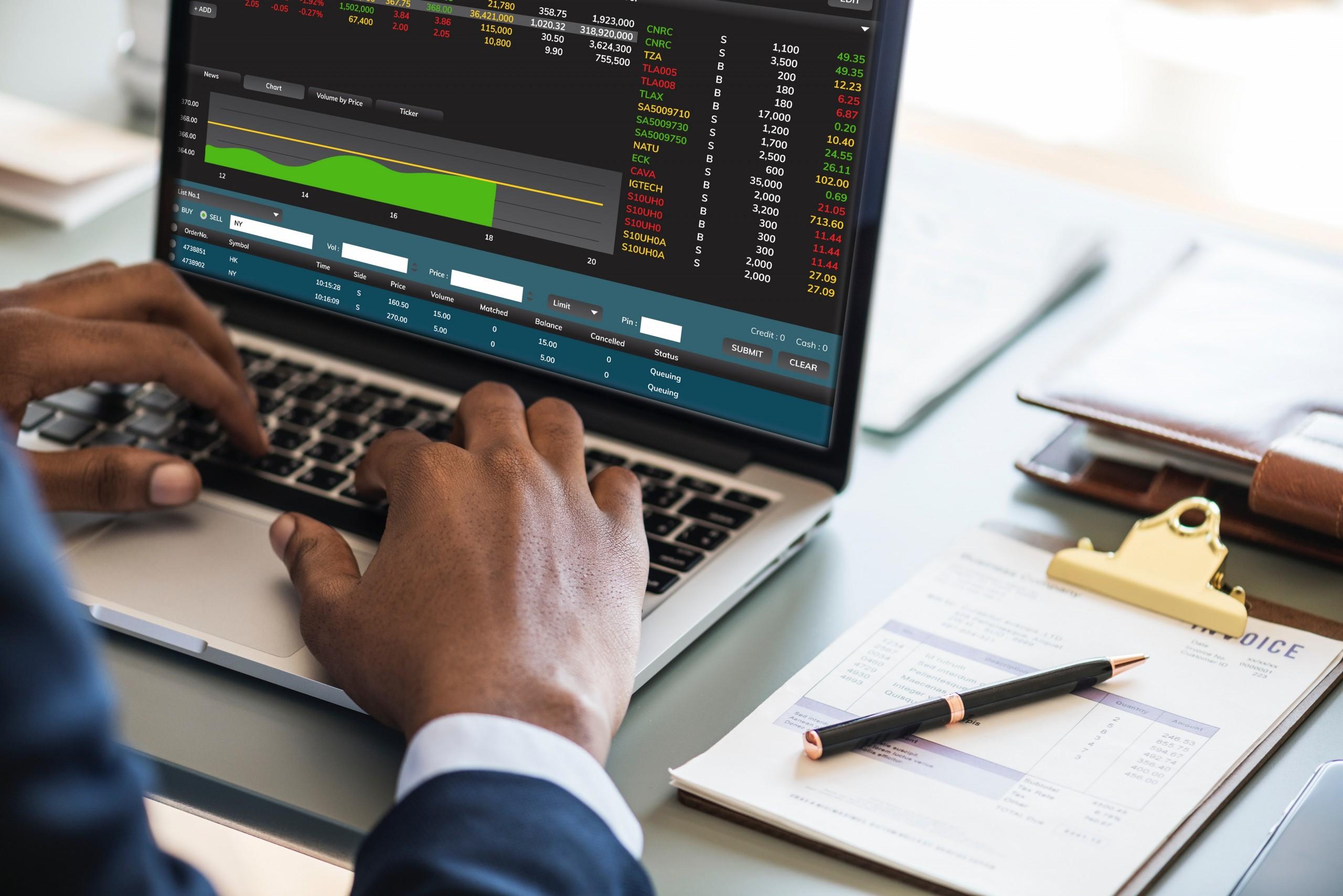 Mãos de um homem vestindo terno mexem em um computador mostrando dados. Ao lado, na mesa, uma caderneta e uma caneta. Entenda como comprovar o cumprimento da LGPD em sua empresa.