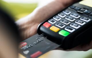 Máquina de crédito com cartão preto inserido para realizar pagamento ilustra artigo sobre como jurisprudência pode ajudar franqueados a superar crise financeira
