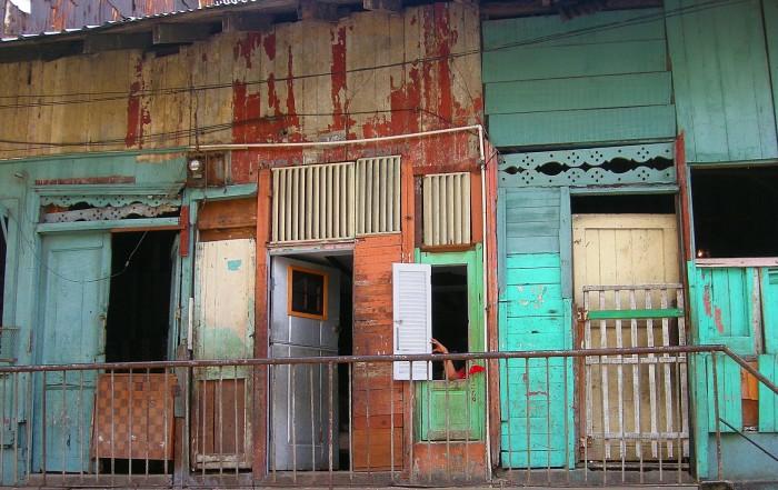 Portas de moradias em uma favela brasileira, pintadas de terracota, azul turquesa e marrom, com a tinta descascando em partes.. O racismo no sistema tributário brasileiro