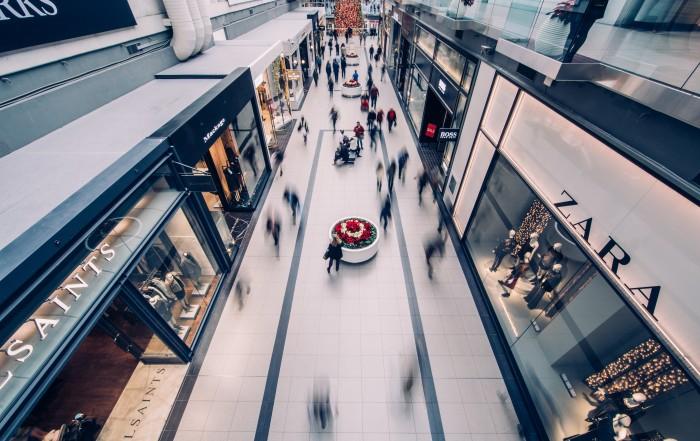 Um corredor de shopping center mostra pessoas andando rapidamente e lojas abertas e iluminadas. Pandemia justifica suspensão de aluguel comercial em 2021.
