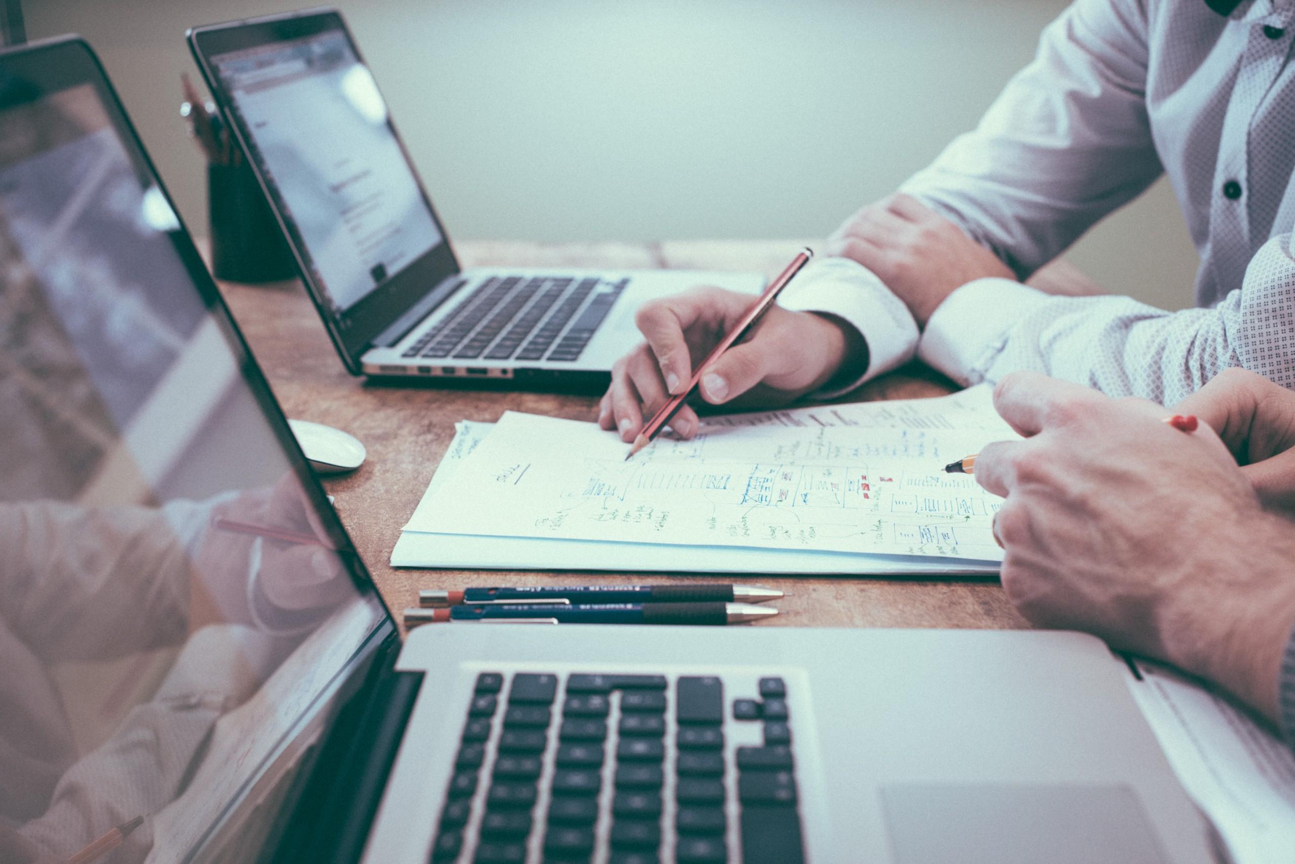 Uma mesa de madeira comporta dois computadores e uma planilha entre eles, com duas pessoas - das quais estão visíveis apenas as mãos - apontam para elementos da planilha. STJ julga alíquota fixa de ISS para LTDA